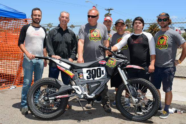 The Monkey Business Baja racing team and Hollywood Electrics are attempting to turn this Zero all-electric motorcycle into a competitive Baja off-road racer. Monkey Business team owner Mark Winkelman (center) spearheaded the project, and is partnering with Hollywood Electrics owner Harlan Flagg (far left) to develop the bike. PHOTO BY SCOTT ROUSSEAU.