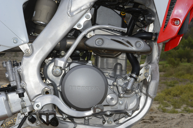 The CRF's liquid-cooled, fuel-injected 249cc Unicam engine sports a new, lighter piston and connecting rod along with titanium valves to cut down reciprocating weight and give it a freer-revving personality. The piston also bumps compression from 13.5:1 to 13.8:1. Revised porting and a new higher-lift cam also increase airflow with the goal of improved performance.