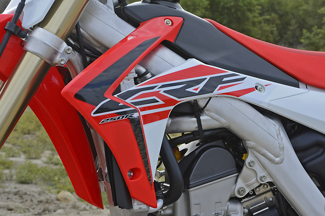 If there's one thing we can stand about the CRF2540R (and CRF450R), it is that their radiator shrouds (and especially those black louvers that protrude just below them) snag boots and kneeguards with reckless abandon during cornering. The situation spoils an otherwise comfortable ergonomic layout.
