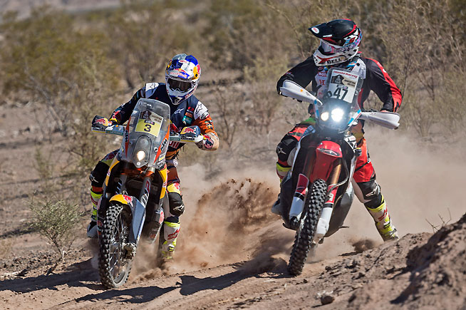 Toby Price (left) battles with Kevin Benavides (right). Price finished second today and continues to enjoy a healthy overall lead. Benavides is now the highest-running Honda rider after Paulo Goncalves withdrew from the rally due to a crash in Stage 11. PHOTO COURTESY OF RED BULL CONTENT POOL.