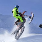 Dashing through the snow! Once you get used to the different riding dynamic of the track, riding a wheelie on a snowbike is no different than on a standard two-wheeler.