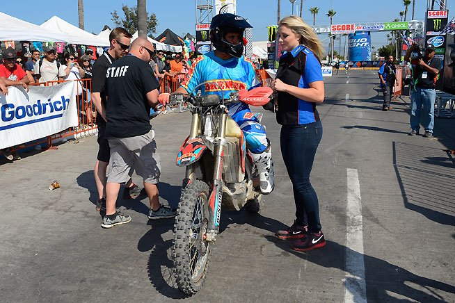 Bremen Honda team owner talks to CBS Sports announcer Dianna Dahlgren after crossing the finish line in Ensenada second overall. The team battled back from hard crashes by two of its riders. The second one involved a collsion with a horse on the race course. PHOTO BY SCOTT ROUSSEAU.