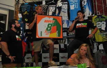 Cooper Abbott (right) explains the special jersey that THOR created for the Destry Abbott Leukemia Fundraiser Event, which was held at Pole Position Raceway in Corona, California. Signed by Destry Abbott and mounted, it topped the evening's auction items, going for $4500. PHOTO BY MARK KARIYA.